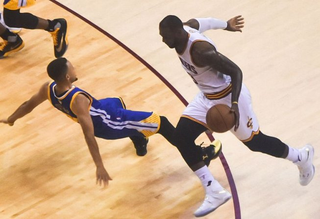 LeBron James drives on Stephy Curry