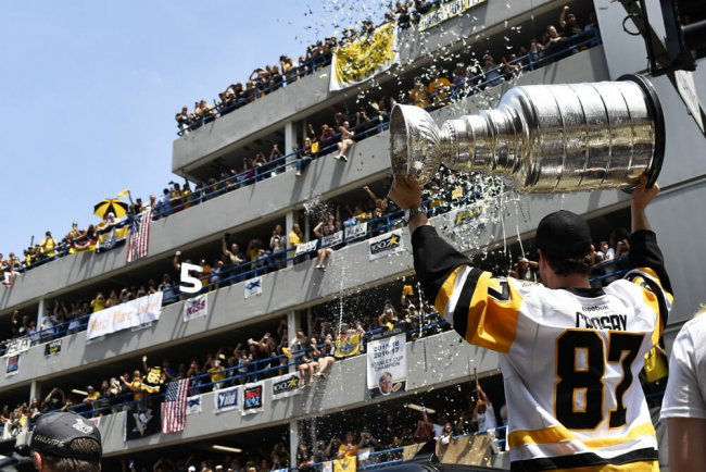 PITTSBURGH, PA - JUNE 14: Pittsburgh Penguins center Sidney Crosby (87) hoists the Stanley Cup in celebration during the 2017 Pittsburgh Penguins Stanley Cup Champion Victory Parade on June 14, 2017 in Pittsburgh, PA.