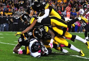 Several Steelers defenders tackle a Texans ball-carrier