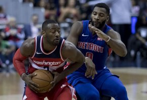Detroit's Andre Drummond attempts to slow down Washington's John Wall
