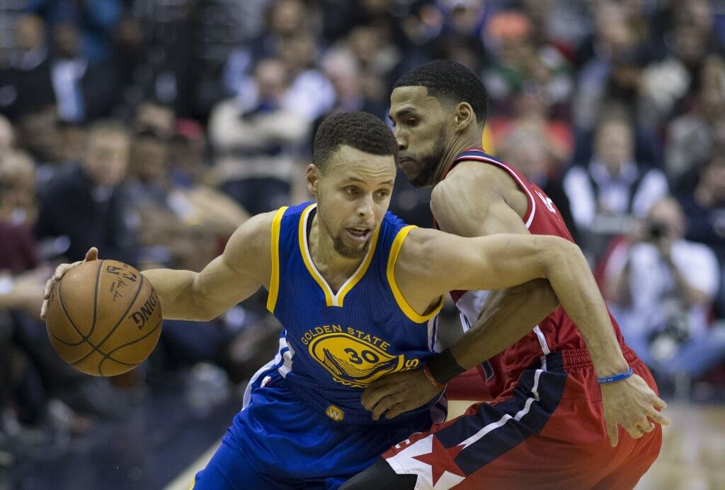 Steph Curry dribbles around a defender