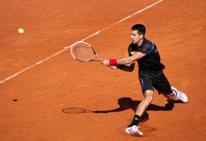 Novak Djokovic hits a backhand at Roland Garros