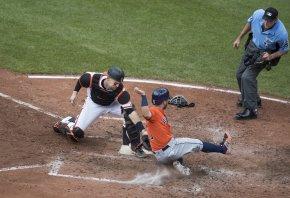Houston Astros second baseman Jose Altuve sliding into home