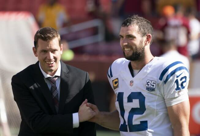 Andrew Luck shaking hands with a man in a suit.